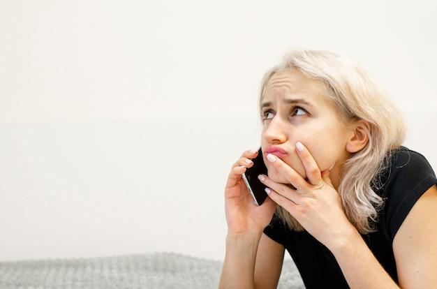 Una giovane ragazza con i capelli biondi comunica al telefono. faccia dispiaciuta. conversazione triste. comunicazione virtuale. senza uscire di casa. sfondo bianco.