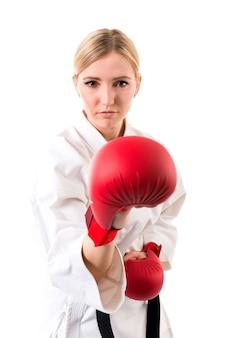 Giovane ragazza con capelli biondi in kimono di karate e guantoni da boxe