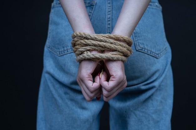 Ragazza giovane con le mani legate su sfondo nero. concetto di violenza della donna. avvicinamento