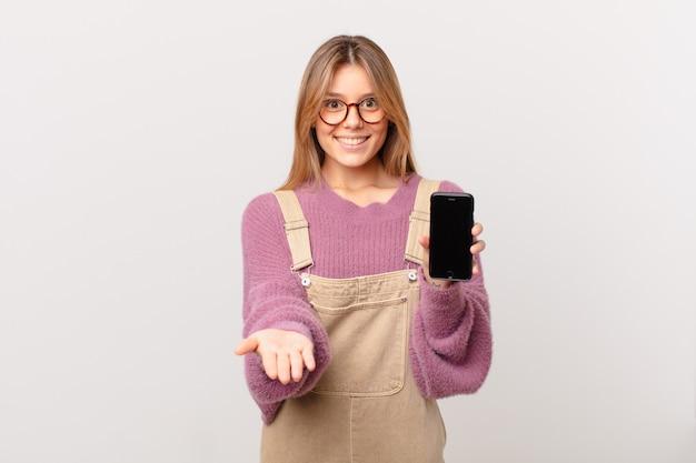 Ragazza giovane con una cella che sorride felicemente con amichevole e offrendo e mostrando un concetto