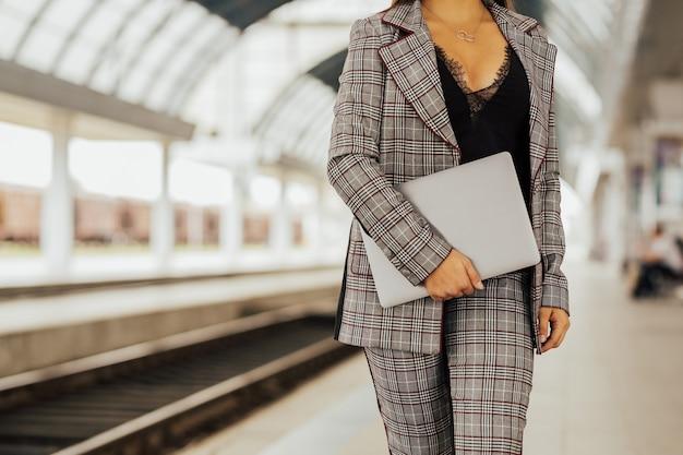 Ragazza giovane con computer portatile chiuso nelle mani in piedi nella stazione ferroviaria urbana