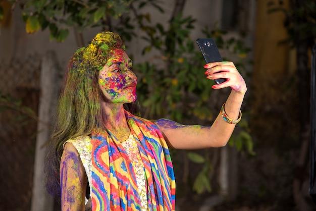 Ragazza giovane con la faccia colorata tenendo selfie utilizza lo smartphone su holi festival. festival e concetto di tecnologia