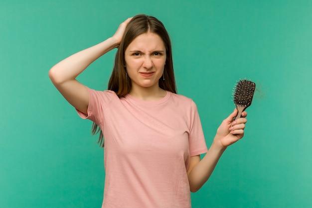 Giovane ragazza con un pettine e capelli problema sull'azzurro