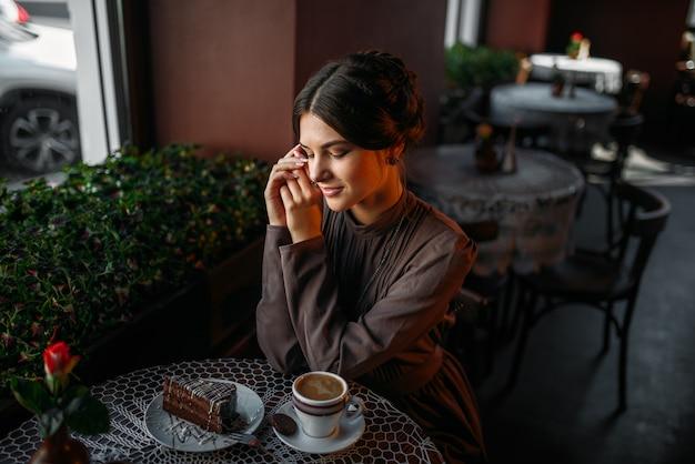 Una giovane ragazza con una tazza di caffè in un caffè retrò