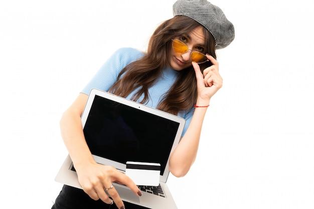 Giovane ragazza con un sorriso delizioso, lunghi capelli castani ondulati, bellissimo trucco, in maglia blu, jeans neri, berretto grigio, occhiali gialli, in piedi con laptop e carta