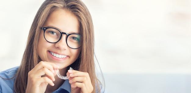 Ragazza giovane con bretelle invisibili dentali.