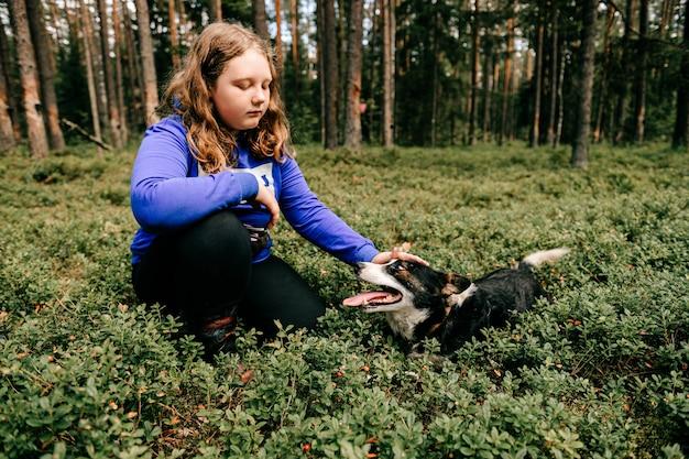 Ragazza giovane con il cane in posa nella foresta