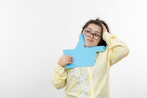 Giovane ragazza con una sindrome di down tenendo il segno della mano