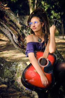Ragazza giovane con i dreadlocks e gli occhiali che si appoggia su un albero e che abbraccia una chitarra acustica. guarda il cielo e sembra molto calma