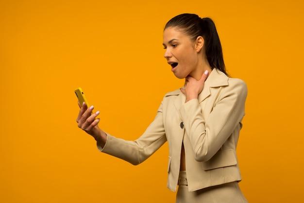 Giovane ragazza con problemi di pelle del viso in posa con uno smartphone su uno sfondo giallo.