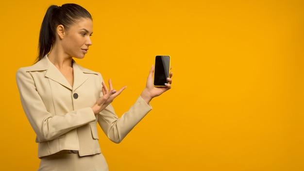 Ragazza giovane con problemi di pelle del viso in posa con uno smartphone su uno sfondo giallo.