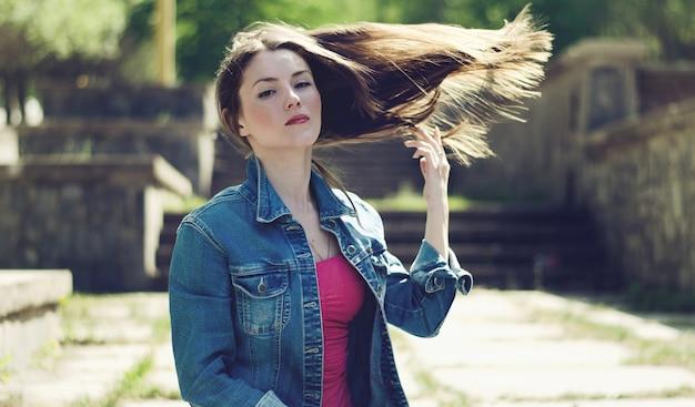 Ragazza giovane con capelli volanti al vento in primavera. stile vintage, tonificante.