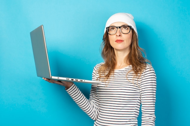 Ragazza con i vetri che porta un cappello bianco che tiene un computer portatile che cerca su un blu
