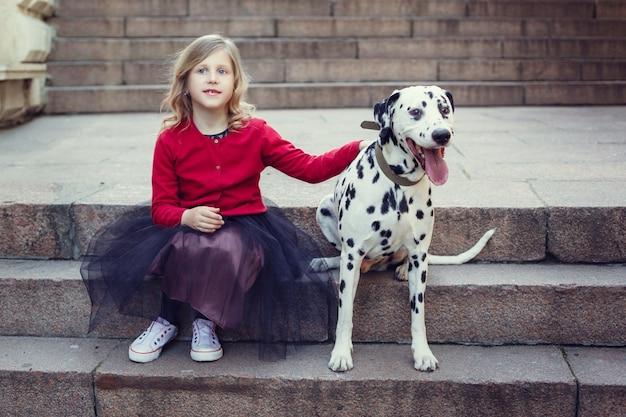 Ragazza giovane con i suoi cani dalmata in un parco di primavera.