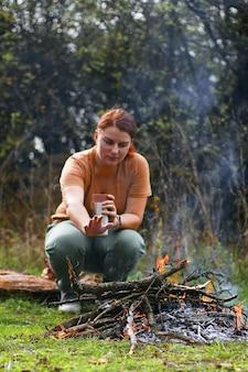 Una giovane ragazza con un thermos di bevanda calda di caffè o tè, si siede su un albero di registro. riscaldarsi accanto al fuoco nella foresta.