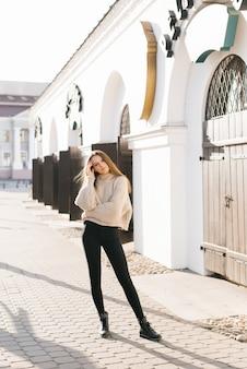 Una giovane ragazza con lunghi capelli castani. indossava un maglione beige e jeans neri attillati.