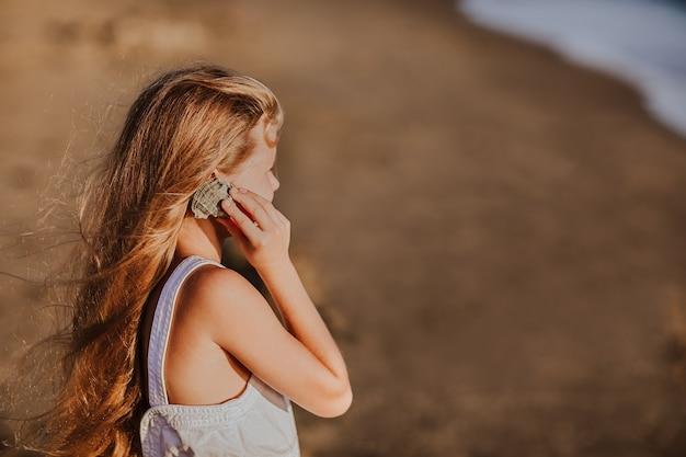Giovane ragazza con i capelli lunghi, tenendo e ascoltando la conchiglia.