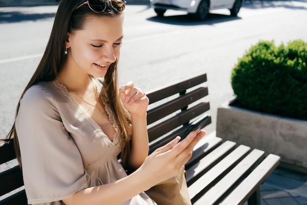 Una giovane ragazza con i capelli lunghi in occhiali da sole si siede su una panca di legno, guarda il telefono. giorno soleggiato