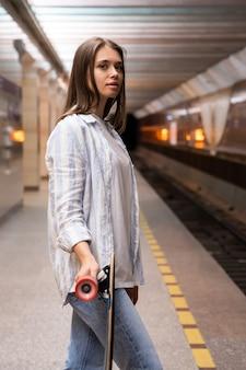 Ragazza giovane con longboard aspetta il treno alla stazione della metropolitana femmina alla piattaforma della metropolitana con skate