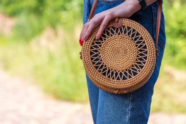 Ragazza con la borsa di paglia rotonda alla moda moderna sulla natura