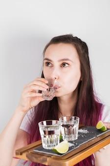 La ragazza con capelli rosa beve il colpo della tequila e tiene il vassoio di legno disponibile con calce, sale e colpi su fondo grigio