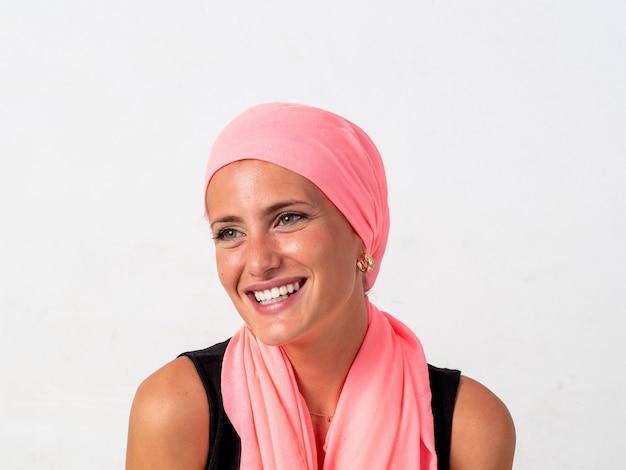 Giovane ragazza con il fazzoletto rosa sulla testa e sfondo bianco, combattendo il cancro