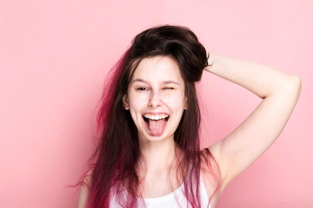 La ragazza con i capelli arruffati rosa senza trucco fa la faccia divertente e attacca la sua lingua su fondo rosa