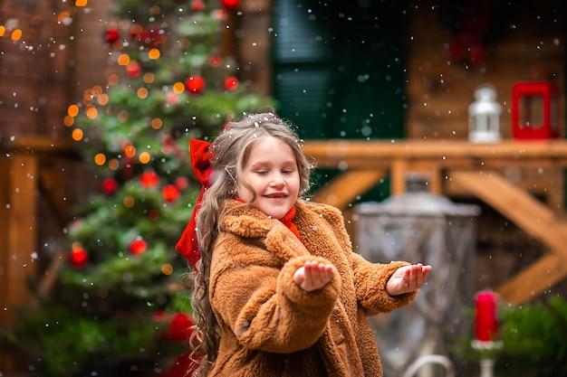 Ragazza giovane con fiocco rosso di natale godendo la nevicata contro l'albero di natale e le decorazioni