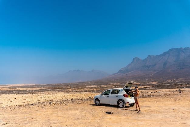 Una giovane ragazza con l'auto a noleggio sulla spiaggia di cofete del parco naturale di jandia, barlovento, a sud di fuerteventura, isole canarie. spagna