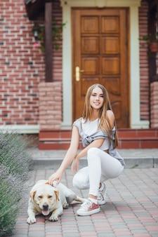 Ragazza giovane con il documentalista in passeggiata davanti alla casa. attraente donna sorridente accarezzando labrador retriever ed esamina la macchina fotografica.