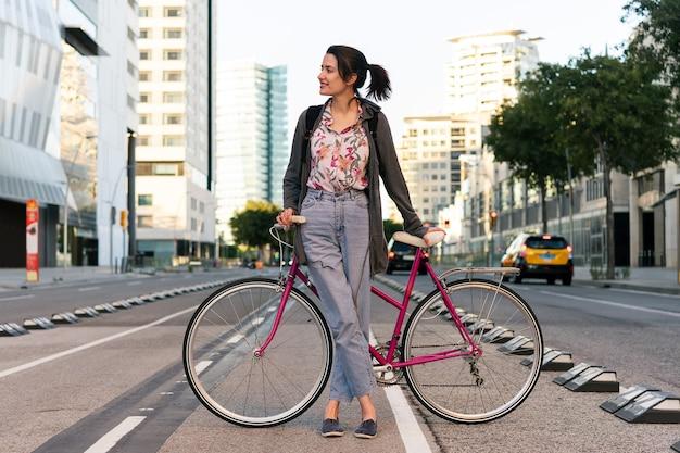 Ragazza giovane con una bicicletta retrò nella pista ciclabile