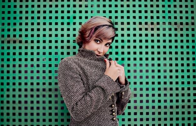 Giovane ragazza con i capelli corti in posa con un cappotto su uno sfondo verde.