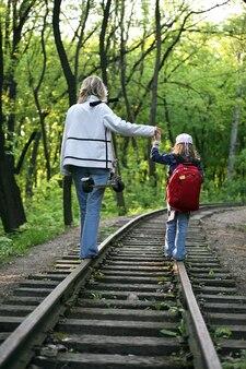 Ragazza giovane con un bambino piccolo che cammina sui binari ferroviari