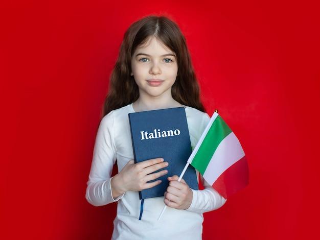 Ragazza giovane con un libro di testo di lingua italiana e una bandiera, scuola di lingue che impara l'italiano