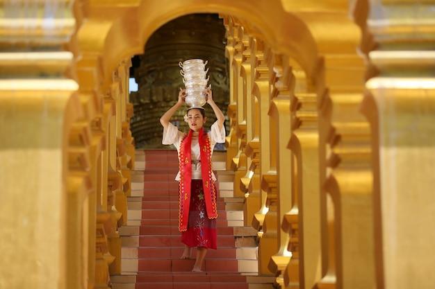 Ragazza giovane con tradizionale birmano tenendo la ciotola di riso sulla mano alla bellissima pagoda dorata in myanmar