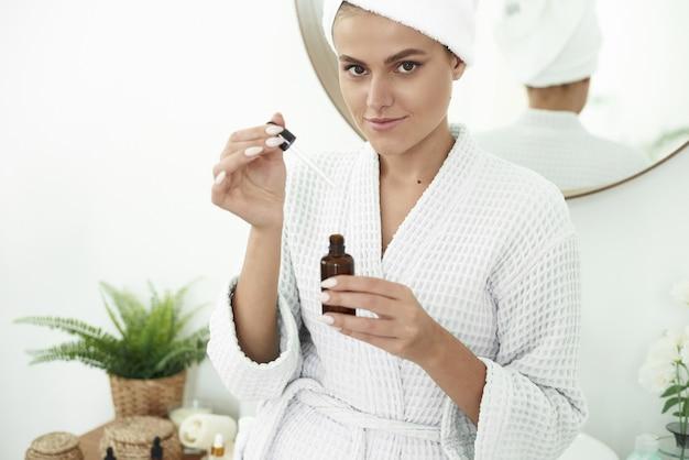 Una ragazza con vitiligine usa un siero idratante e si lascia cadere una goccia sulle mani
