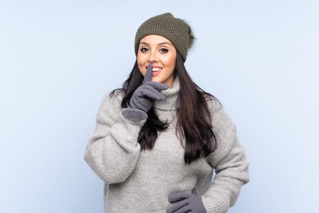 Ragazza con il cappello di inverno sopra il gesto facente blu di silenzio