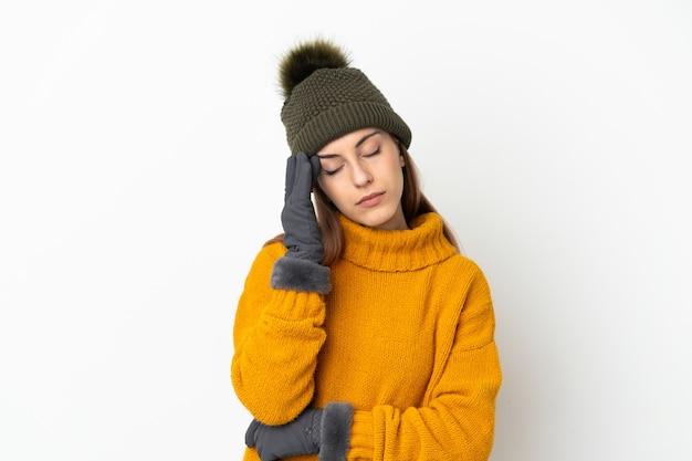Ragazza giovane con cappello invernale isolato su sfondo bianco con mal di testa
