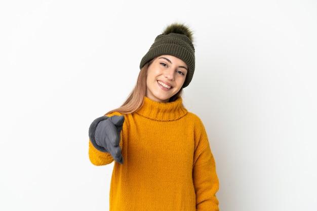 Giovane ragazza con cappello invernale isolato su bianco stringe la mano per chiudere un buon affare