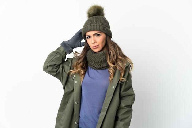 Giovane ragazza con cappello invernale isolato sul muro bianco che ha dubbi