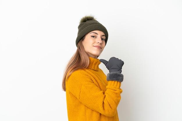 Giovane ragazza con cappello invernale isolato sul muro bianco orgoglioso e soddisfatto di sé