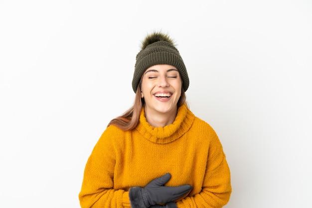 Ragazza con cappello invernale isolato sul muro bianco sorridente molto