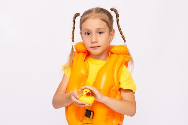 Giovane ragazza con giubbotto di salvataggio giallo e paperella di gomma su sfondo bianco.