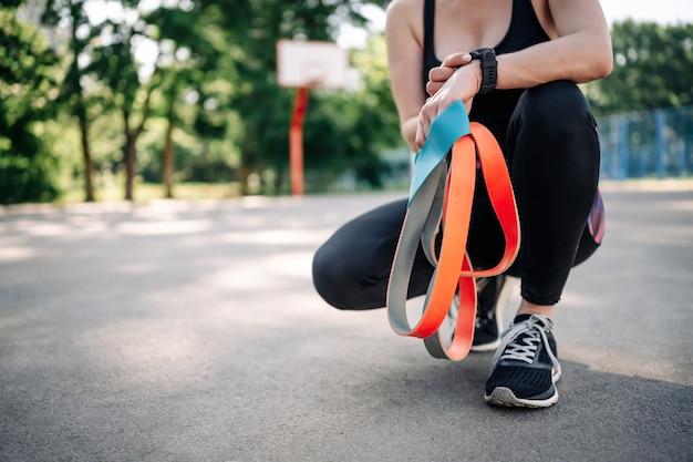 Giovane donna che indossa abbigliamento sportivo allo stadio e tiene tra le mani un set di elastici in gomma g...