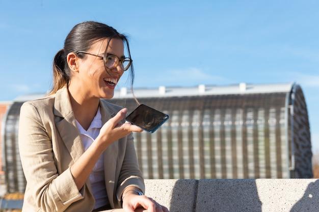 Ragazza che lavora su una panchina del parco fuori dal suo ufficio parlando sul suo telefono cellulare. concetto di business, tecnologia e telelavoro.