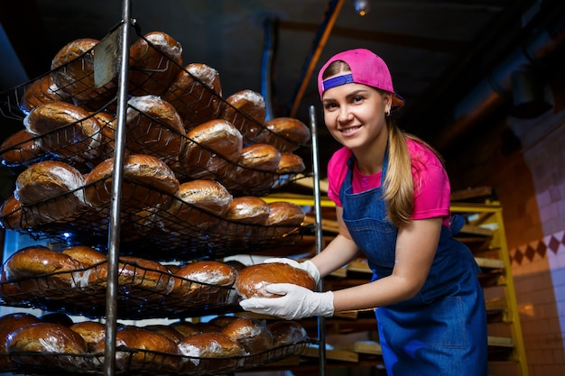 Una ragazza lavora in una panetteria. mette il pane su uno scaffale. fornaio donna sul posto di lavoro in una panetteria. un fornaio professionista tiene il pane nelle sue mani. concetto di produzione del pane