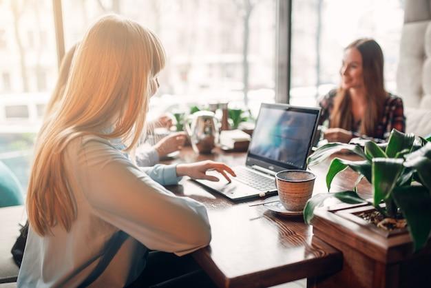 Giovani amiche guarda le merci sul computer portatile, presentazione aziendale nella caffetteria, marketing. moderne tecnologie pubblicitarie