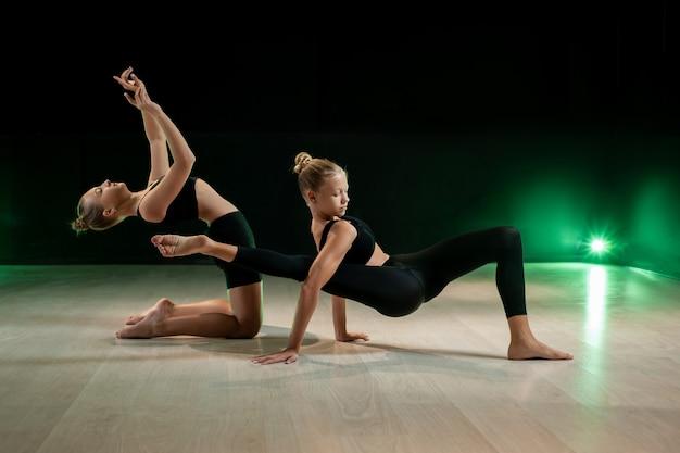 Le ragazze che ballano in studio su uno sfondo scuro