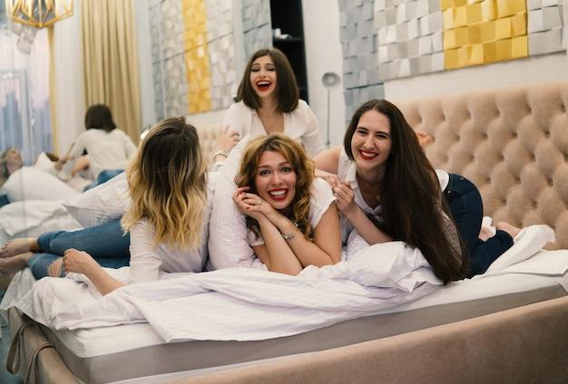 Amici delle ragazze che combattono i cuscini in camera da letto. loro si divertono