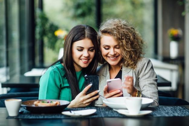 Giovani amiche che trascorrono del tempo insieme bevendo caffè al bar, facendo colazione e dessert. gioventù, stile di vita, concetto di comunicazione, usando i loro telefoni.